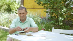 Man puts tobacco into his pipe. Stock Footage