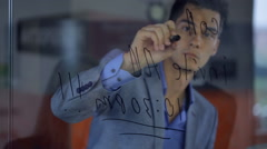 Young man businessman writes with marker on transparent glass, giving lessons to - stock footage