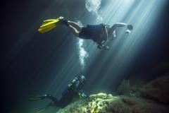 A young married couple scuba diving in Devil's Den Springs Florida. Stock Photos