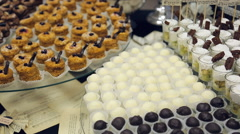 Banquet table and laid out a variety of small cakes, candies, white and dark - stock footage