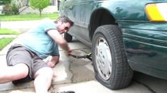 Man Changing Tire with Jack Stock Footage