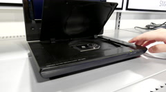 Hand insert and eject a dvd in a player inside best buy store - stock footage