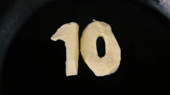 Countdown animation from 10 to 0 of butter in shape of numbers on hot pan Stock Footage