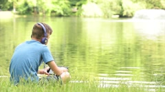 Teen boy with tablet pc and headphones listening to music or watching video - stock footage