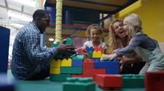 4K Happy family having fun knocking down building bricks at indoor playground Stock Footage