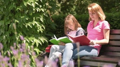 Mother and daughter reading books - stock footage