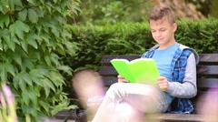 Teen boy reading book Stock Footage