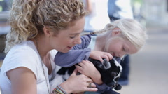 4K Families visiting a community farm, woman with daughter petting cute goat Stock Footage