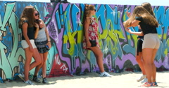 Young girls take pictures near graffiti wall in Venice Beach in Los Angeles, 4K Stock Footage
