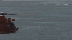 Coast Guard Helicopter Retrieves a Victim In a Rescue Basket Stock Footage