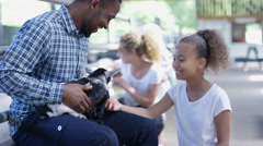 4K Families visiting community farm, man with daughter petting cute little goat Stock Footage