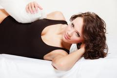 Sexy girl lazy woman with pillow on bed in bedroom Stock Photos