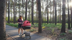 Mother with baby in buggy walking in park Stock Footage