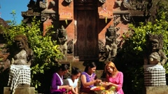 Women making Canang sari offerings in front of balinese temple gates Stock Footage