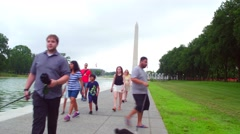 Washington Monument Reflection Pool with people passing by Stock Footage