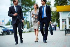 Happy business people walking along the street and drinking takeaway coffee Stock Photos