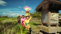 Small balinese procession going to temple between rice fields Stock Footage
