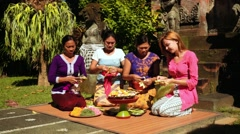 Balinese women making offerings with tourist Stock Footage