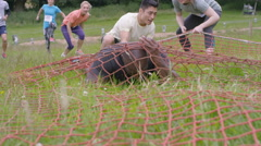 4K Competitors in assault course race running & crawling under net on ground Stock Footage