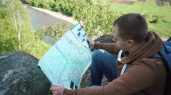 Young tourist man checking his route with map while sitting on shadowed rock Stock Footage