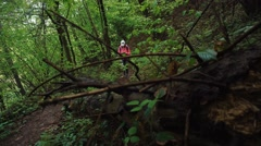Serious active female tourist navigates in summer forest trail with a paper map Stock Footage