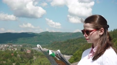 Young woman in sunglasses looking to her map standing at highland with rural Stock Footage