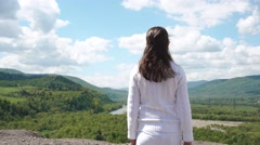 Young woman walking to the hill's edge and spreading her hands wide feeling free - stock footage