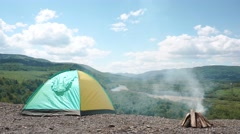 Camp site with bonfire on rocky top of hill in green mountains Stock Footage