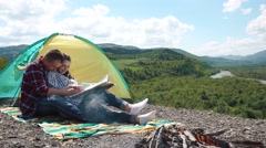 Young tourist couple have a sensual moment sitting in camping. Beautiful young - stock footage