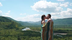 Young couple covered in lined blanket holding each other on the top of the hill Stock Footage