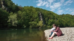 Young couple, handsome young man and pretty girl dropping stones in water sittin Stock Footage
