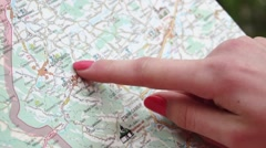 Young woman drawing her finger on map, checking her way and then walks towards Stock Footage