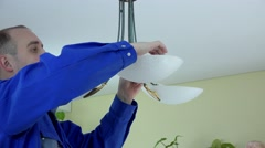 Skilled electrician install eco light bulbs in chandelier at client home - stock footage