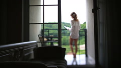 Relaxed woman in the morning reading her book on balkony. View from darkened Stock Footage