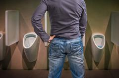Standing man peeing to a urinal in restroom or incontinence concept - stock photo