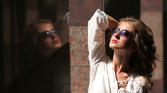 Pretty young blonde woman in sunglasses and white blouse standing in the Stock Footage