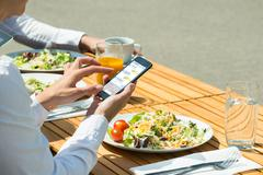 Person Chatting On Mobile Phone With Food And Glass Of Juice On Table - stock photo
