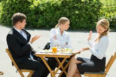 Group Of Three Young Businesspeople Having Argument In Restaurant - stock photo