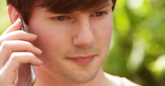 4k,Attractive young man in the park talking on his mobile phone. Stock Footage
