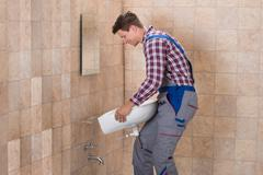 Side View Of Happy Male Plumber Installing Sink In Bathroom Stock Photos