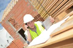 Foreman using walkie-talkie and digital tablet on construction site Stock Photos