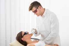 A Male Therapist Giving Laser Epilation Treatment On Woman's Face Stock Photos