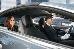 Beautiful Young Woman Traveling In A Car With Male Handsome Chauffeur - stock photo