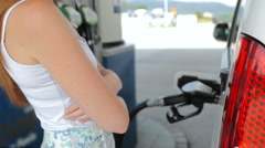 Woman filling-up car gasoline tank waiting beside 4K Stock Footage