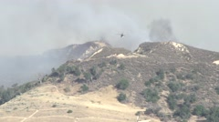 Firehawk helicopter makes ground-skimming approach and water drop (Sand Fire) Stock Footage