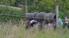 4K Competitors in endurance race, helping each other through tyre obstacle Stock Footage