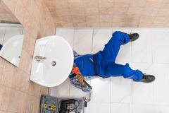 High Angle View Of Male Plumber Repairing Sink In Bathroom Stock Photos
