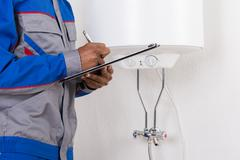 Close-up Of Male Plumber Writing On Clipboard Stock Photos