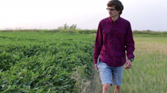 Young farmer goes in the field and evaluates crop Stock Footage