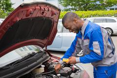 Happy Mechanic Using Multimeter To Check The Voltage Level In A Car Battery Stock Photos